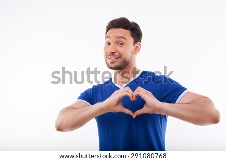 Attractive guy is making a heart shape symbol with his fingers. He is smiling because he loves.  Isolated on a white background and there is copy space in the left side - stock photo