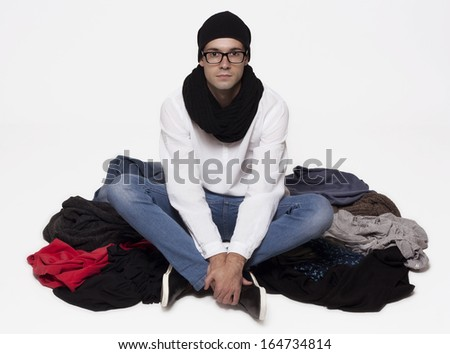 Attractive guy sitting cross-legged in a pile of clothes isolated on white background. - stock photo