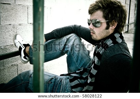 attractive guy sitting with his sunglasses and scarf