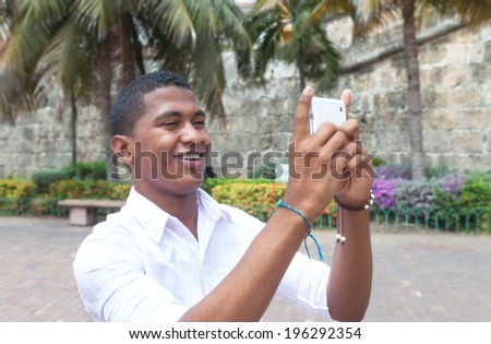 Attractive guy taking a picture with phone  - stock photo