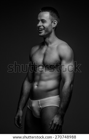 Attractive guy with naked torso smilin. Black and white photo. Isolated on grey