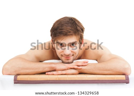 attractive handsome man smile resting in a spa massage center, lying on table relaxing isolated over white background with copy space, concept of men beauty health care - stock photo