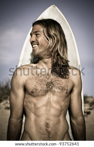 Attractive handsome muscular long haired surfer posing with his surfboard behind him. Metallic, cold feel. - stock photo