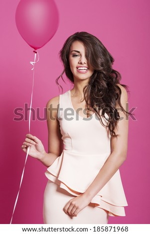 Attractive happy brunette women with pink balloon - stock photo