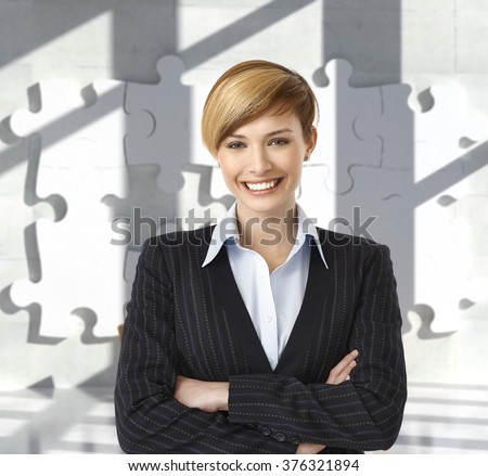 Attractive happy caucasian blonde female business office worker. Portrait, toothy smile, standing, looking at camera, arms crossed, woman suit, jigsaw puzzle background. - stock photo