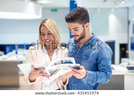 Attractive happy couple looking at a catalogue in a store. - stock photo