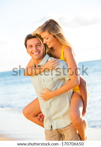 Attractive Happy Couple Playing on the beach at Sunset