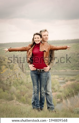 Attractive happy couple posing in the wilderness standing on a grassy hill in a close embrace with the attractive young woman smiling happily as she playfully holds her arms extended sideways - stock photo