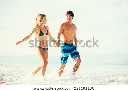 Attractive Happy Couple Running and Playing on Beautiful Sunny Beach  - stock photo