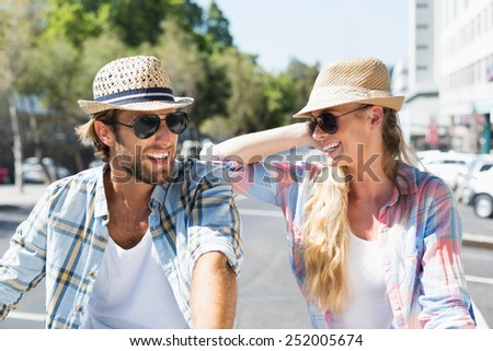 Attractive happy couple wearing sunglasses on a sunny day in the city - stock photo