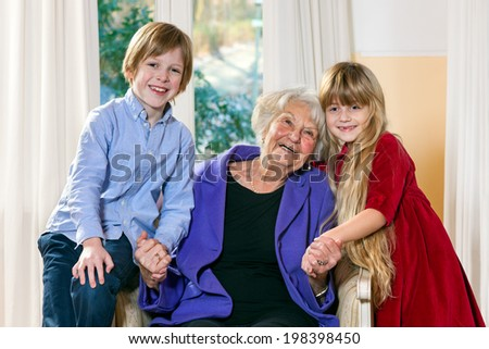 Attractive happy little boy and girl with their grandmother posing with her in the living room as they hold hands and touch heads tenderly while smiling happily at the camera - stock photo