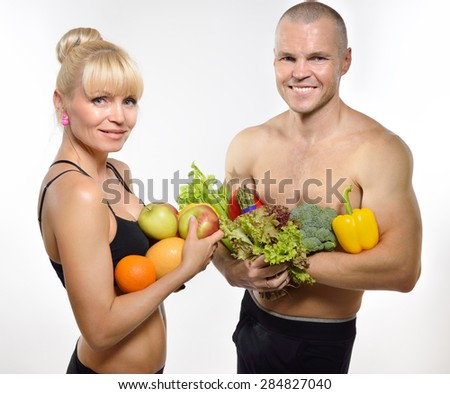 Attractive happy middle-age fit man and woman holding fruit and vegetables. Healthy eating, fitness, diet, vegetarianism and rawfoodist concept. - stock photo