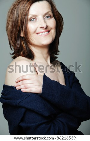 Attractive happy middle-aged woman in black dress. - stock photo