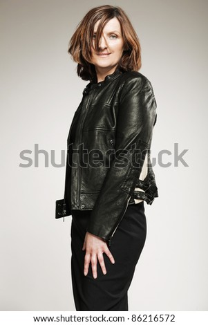 Attractive happy middle-aged woman in black jacket. - stock photo