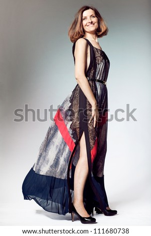 Attractive happy middle-aged woman in long dress. - stock photo