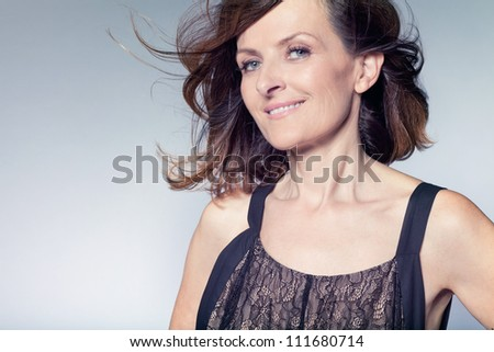 Attractive happy middle-aged woman with curly hair. - stock photo