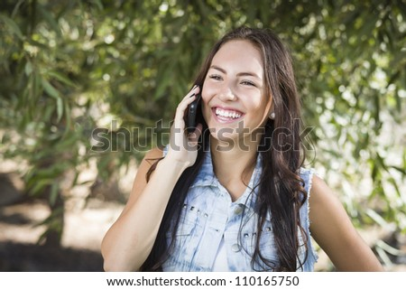 Attractive Happy Mixed Race Young Female Talking on Cell Phone Outside.