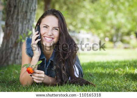 Attractive Happy Mixed Race Young Female Talking on Cell Phone Outside Laying in the Grass. - stock photo
