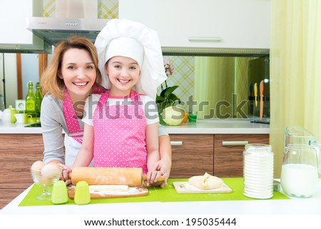 Attractive happy mother and daughter baking together at the kitchen. - stock photo