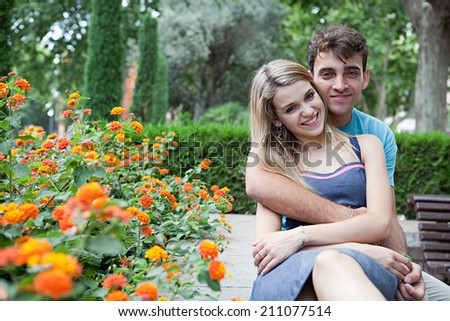 Attractive happy romantic young couple holding hands in a park with flowers, enjoying a day together on holiday. (Love, Lifestyle, outdoor) - stock photo