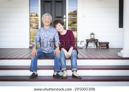 Attractive Happy Senior Chinese Couple Sitting on the Front Steps of Their House. - stock photo