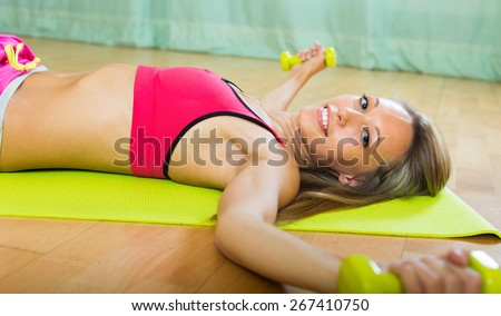 Attractive happy smiling girl working out at home  - stock photo