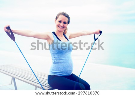 Attractive happy smiling pregnant woman exercising with resistance ropes to strengthen and tone her muscles in a health and fitness concept - stock photo