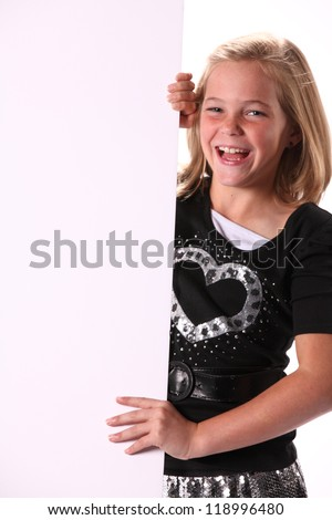 Attractive happy smiling preteen 10 year old female girl holding a white sign isolated against a white background.