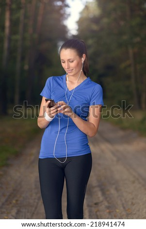 Attractive happy woman standing listening to music on a dirt track through a forest with her MP3 player and earplugs with a smile of pleasure on her face - stock photo
