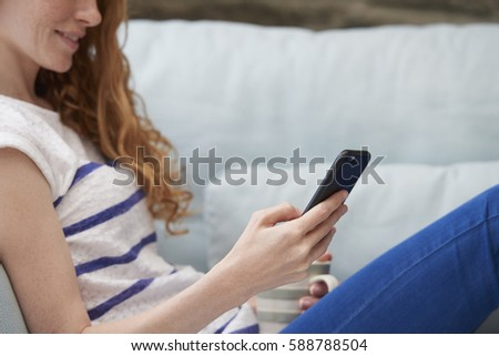 Attractive happy woman using smart phone technology at home drinking coffee browsing internet social media