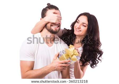 Attractive happy woman with big toothy smile holding boyfriends eyes giving him a present for Valentine's day. Girl look at man. Caucasian couple. White background. - stock photo