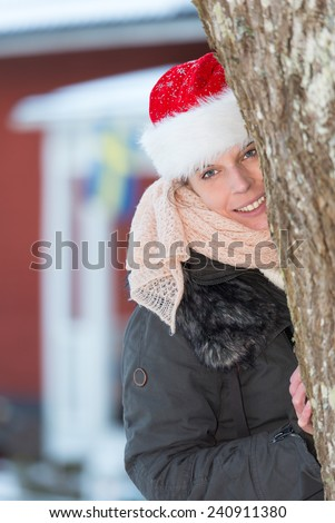 Attractive happy woman with santa claus hat looking from behind a tree i front of a typical red wooden house in Sweden.