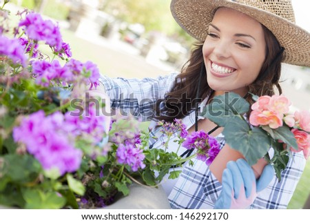 Attractive Happy Young Adult Woman Wearing Hat Gardening Outdoors. - stock photo