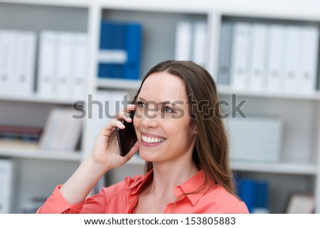 Attractive happy young businesswoman chatting on a smartphone in the office with a delighted smile on her face