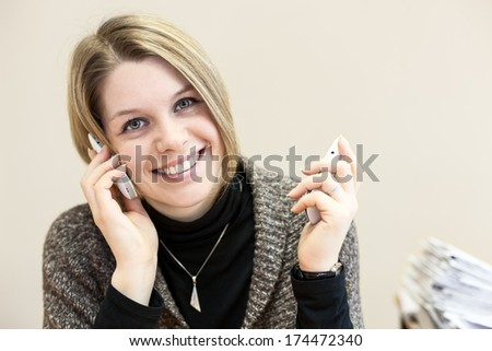 Attractive happy young businesswoman chatting on two smartphones in the office - stock photo