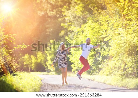 Attractive happy young couple having fun outside in a park