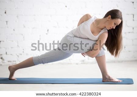 Attractive happy young woman working out indoors. Portrait of beautiful model doing exercises on blue mat in room with white walls. Revolved Side Angle Pose, Parivrtta Parsvakonasana. Full length - stock photo