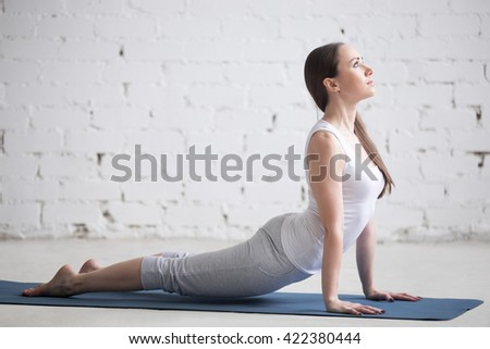 Attractive happy young woman working out indoors. Side view portrait of beautiful model doing exercises on blue mat. Standing in upward-facing dog pose, urdhva mukha svanasana. Full length - stock photo