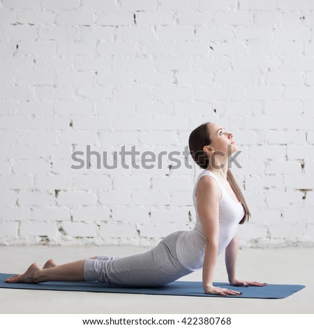 Attractive happy young woman working out indoors. Side view portrait of beautiful model doing exercises on blue mat. Standing in upward dog pose, urdhva mukha svanasana. Full length. Square image - stock photo