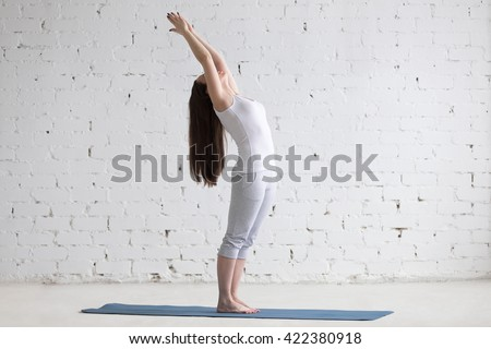 Attractive happy young woman working out indoors. Side view portrait of beautiful model doing yoga exercise on blue mat. Standing backbend or variation of Tadasana. Full length - stock photo