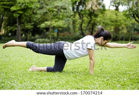 Attractive Healthy Asian Woman doing yoga in the park