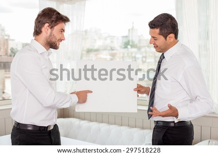 Attractive healthy businessmen are holding a white board and looking at it with concentration. They are standing and discussing some concepts. The man is pointing his finger at it and smiling - stock photo