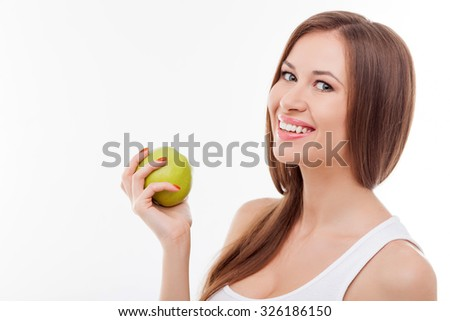 Attractive healthy girl is eating green apple. She is holding fruit and smiling. The lady is standing and looking forward happily. Isolated and copy space in left side
