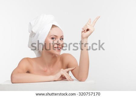 Attractive healthy girl is leaning on white surface and relaxing after shower. She is pointing her finger up and smiling. The lady has towel over her head. Isolated and copy space in right side - stock photo