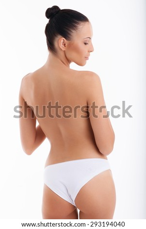 Attractive healthy girl is showing her naked back. She is wearing white panties. The lady is looking down with enjoyment. Isolated on background - stock photo