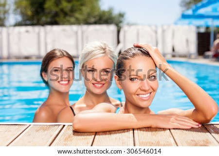 Attractive healthy girls are swimming in pool. They are looking forward and smiling. The brunette girl is leaning on the board and resting - stock photo