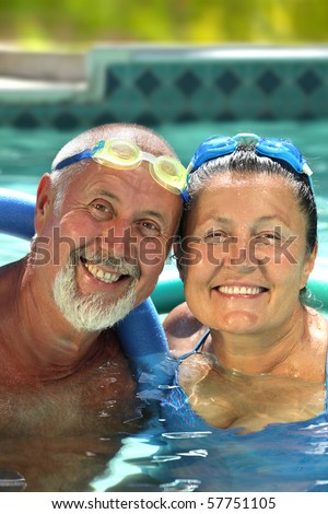 Attractive, healthy older couple swimming together