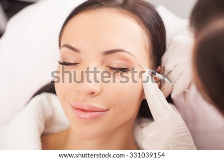 Attractive healthy woman is getting botox injection and smiling. Her eyes are closed with pleasure. The expert beautician is filling hyaluronic acid into female face with syringe - stock photo
