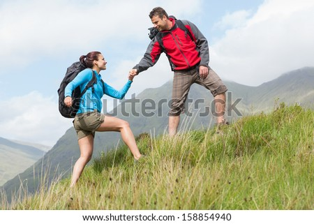 Attractive hiker helping his girlfriend uphill in the countryside - stock photo