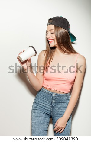 Attractive hipster girl is holding a cup and drinking coffee. She is looking at it and smiling. The girl is wearing a cool black cap. Isolated on background - stock photo